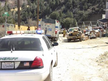 A sheriff's deputy keeps traffic from entering the area near the gas leak while fire crews are on scene waiting for a gas company representative to arrive. [photo by The Mountain Enterprise]