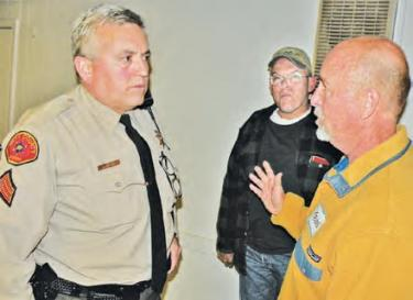 On March 5 Sergeant Mark Brown listens to Kevin Lundin tell of security concerns in Piñon Pines. [Hedlund photo for The Mountain Enterprise]