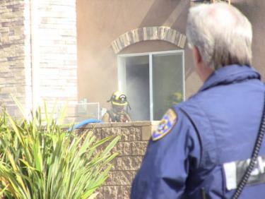 A CHP officer observes as a Kern County firefighter works to extinguish a small fire at Holiday Inn Express in Lebec. [photo by The Mountain Enterprise]