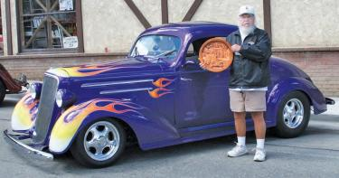 This flaming purple delicacy was chosen Best of Show for 2012—a 1936 Chevrolet. The owner holds Mountain Community artist John Grubb's hand-carved trophy. [Chuck Noble photo]
