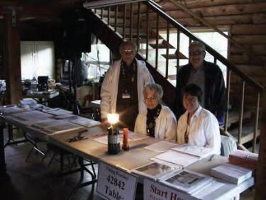 Pine Mountain poll workers opened at 6:30 a.m. by lantern light. (l-r) Marv and Joan Ehrlich, Mary Jayne Glaseman and Gary Cadwallader bask in the glow of their gas lantern. [photo by The Mountain Enterprise]