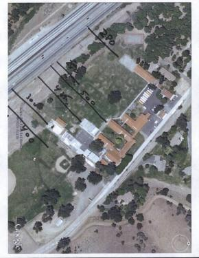 An aerial view of El Tejon School and the Interstate 5 freeway, showing the distance from the freeway to playing fields and school buildings is 250 to 500 feet. Analysts say emissions diminish at about 1,000 feet from such a source of emissions. [National Geological Survey ]