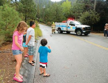 Jillian Otash,10; Tristan Clint, 10; Kirstin Clint, 6; and Preston Clint, 4 stood well back from the road block as firefighters up the road kept the high voltage fire on Matterhorn from spreading until the power company arrived.