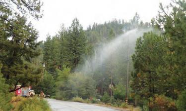 The rains started Saturday afternoon,Aug. 11 quickly turning to torrents down Pine Mountain community streets. Kern County firefighters released water on the high voltage pole fire in short bursts, to avoid allowing the electricity a path down the water to the fireman.