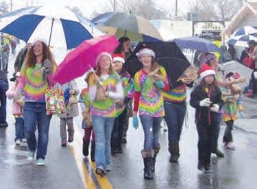 Girl Scouts marched and skipped with big smiles under umbrellas. [Meyer/Hedlund photos]