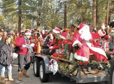 Santa showed up to Pine Mountain Village on his North Pole Transit John Deer tractor sleigh. Ashley Bates had written him a letter. Santa took Ashley's letter. She asked for a coloring book, markers and new mittens. Then all the elves marched with Santa to the village gazebo.