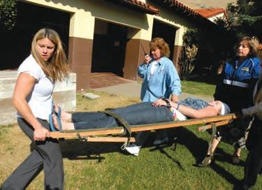 Sara Haflich, Chris Penella and Dina Kiouses carry Katy Teare to the El Tejon triage area in 2008 safety drill.  [Hedlund photo]