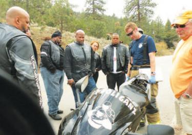 What to do with the Hooliganz motorcycle left behind when Brandy went to Henry Mayo Medical Center was the question a firefighter, a Bakersfield passerby and the Hooliganz are discussing here. [Hedlund photo]