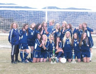 The 2008 FMHS Girls Soccer Team clowning behind some very large trophies. Front row (l-r): Elena Nommensen, Ann Kashanski, Lexi Hughes, Cassandra Zing-Acuna, Shelly Birtell, Kacie Sanders, Becca Hart. Back row (l-r): Coach Lemburg, Danielle Culver, Torri Barrington, Amelia Nommensen, Danielle Sturdevant, Callie Willoughby, Jenny Karson, Cheyenne Thompson, April Beaux, Kaleigh Gentry, Ashley Lynn.