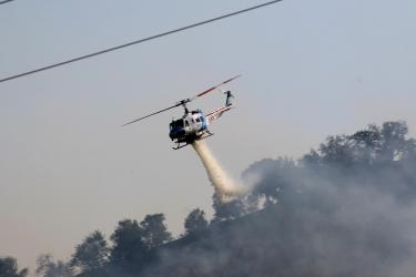 Kern County's helicopter 408 drops water on the fire at Lebec Oaks Road Thursday afternoon. [Chuck Noble photo]