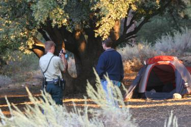 Crime investigators examine the area around the camping tent before examining the body inside. [photo by Gary Meyer]