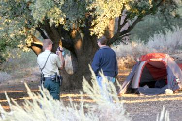 Crime investigators examine the area around the camping tent before examining the body inside. [Meyer photo]
