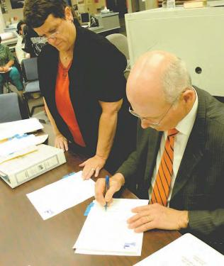 ETUSD Financial Manager Terri Geivet helps Interim Superintendent Mark Fulmer sign five layoff letters on May 13.