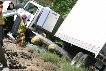 Kern County Fire crew members from Station 55 and 56 work to remove debris from around a big rig that crashed in Gorman on Thursday, May 28. [Meyer photo]
