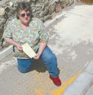 Linda Hawkins shows her $255 ticket and the yellow pads near the affected curb, nearly covered with sand.
