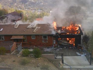 View of Blanche Farnum's home on Idaho Trail in Frazier Park as it burned Sunday, Oct. 18, 2009. The fire was reported at about 7:20 a.m. Two explosions brought the neighbors running to her aid. [Christian Suorsa photo]