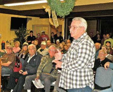 An overflow crowd gathered beneath holiday decorations in the Pine Mountain Club Condor Room for the December 19 PMCPOA Board meeting. Gary Biggerstaff said community members would conduct their own task force to look into more than security patrol issues.