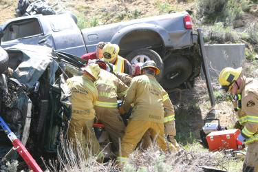 Kern County and Los Angeles County firefighters work together to remove one deceased occupant from a sedan before they were able to free an injured victim who was airlifted to a hospital in Los Angeles County. [Photo by Gary Meyer of The Mountain Enterprise]