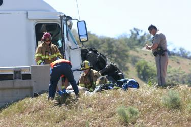 An injured trucker is attended to by a Hall Ambulance paramedic and Kern County firefighters. [Photo by Gary Meyer, The Mountain Enterprise]