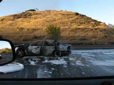 As Throckmorton passed he wa able to take this photo of the car, covered in fire suppressant foam. The dry grass on the hillside was prevented from catching fire by LACFD's quick action.