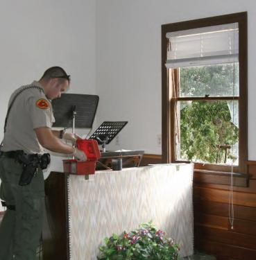 Deputy Kevin Moretti seeks fingerprints at the scene of the break-in. A rock was thrown through the window.