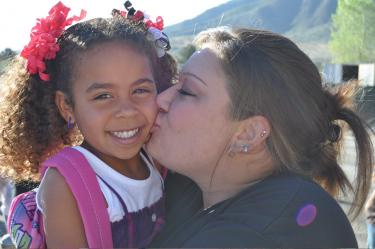 Danielya finally accepts the avalanche of kisses that her mom, Jackie, bestows as first day of school good luck.