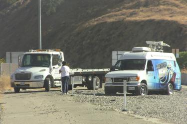 A Channel 29 News van tried to approach the fire command post by driving up the runaway truck ramp, which--the driver discovered--is full of large pea gravel designed to stop vehicles from going forward. [photo by The Mountain Enterprise]