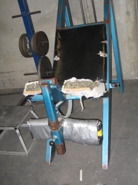 At the high school, previous, the upholstery on the weight bench is shredded and, above, the weight machines are held together with duct tape in a dim workout room.