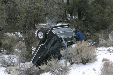 Michael Stevens of Canyon Country goes back down to his SUV to collect belongings after overturning the vehicle on an icy Frazier Mountain Park Road Sunday morning. [photo by The Mountain Enterprise]