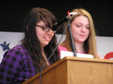 8th grade students Mariana Martinez and Kalie Morgan speak at a Gorman School Veterans Day assembly.