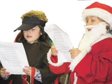 Santa visited Frazier Park School just before winter vacation. Catlyn Moser sports the white beard and Kelsy Zumga plays the title role in the play Olive the Other Reindeer.