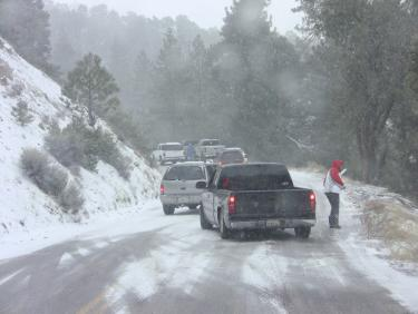 Vehicles headed out of Pine Mountain were stuck on Mil Potrero Highway. Numerous drivers stopped in the middle of the highway to install chains. [photo by The Mountain Enterprise]