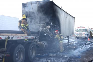 Firefighters work to put out the fire that engulfed the cab of the truck carrying metal pipes. It rammed into the back of a big rig carrying wood chips at about 1:20 p.m. Thursday, Jan. 6. Pipes scattered across the road, delaying access by firefighters and ambulance crews.