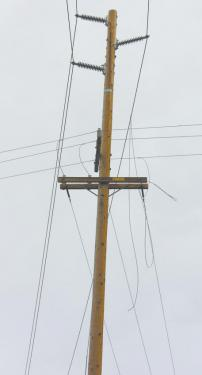 A guy-wire which was snapped during a vehicle accident flew on top of this pole's power lines, causing a short. This resulted in loss of power to homes and businesses throughout the mountain area. [photo by The Mountain Enterprise]