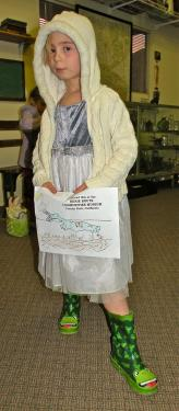 Katelyn shows off her coloring page of the condor, along with her velvet-chiffon party dress and froggie boots.