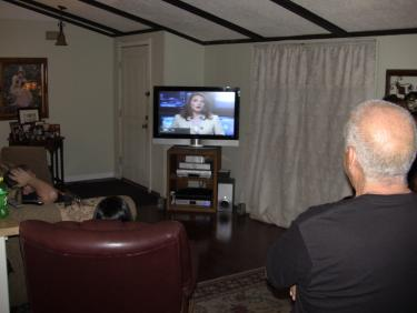 Saldana and his family watch a Bakersfield television news report about his alleged employment termination. [photo by The Mountain Enterprise]