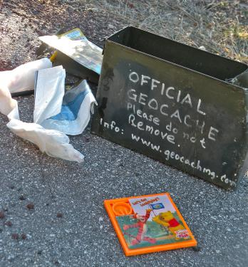 A robot with a water cannon was deployed to blast the ammo case. Nothing exploded. What popped out was childrens toys. The note inside the lid of the ammo box said: Geocache­­­­—Please Read. CONGRATULATIONS! You've found a geo-cache. It's part of a worldwide game using GPS units. There are more than 300,000 caches all over the world. We hide these and find others. If you found it by accident—welcome to a cool sport. Join the fun on the web www.geocaching.com. It's free! Please sign the log and, if you want, make a trade. Don't vandalize or steal this cache... [the rest of the note is obliterated from the water cannon's explosion].