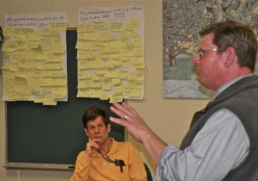 With brainstorm boards on the wall behind him, Trustee Ken Hurst listens to Buck Weber and Dena Kiouses (not shown) report on the March 16 focus group. About 50 parents participated in this first event.