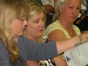 Treasurer Lori Hallmark, former board member Barbara Stowell and new president Lisa Johnson look over membership forms during a packed FMHS Booster Club meeting.