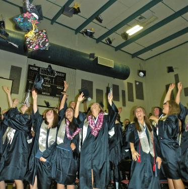 Tossing the mortarboards into the sky after the ceremony is an honored tradition. [Hedlund Photos]