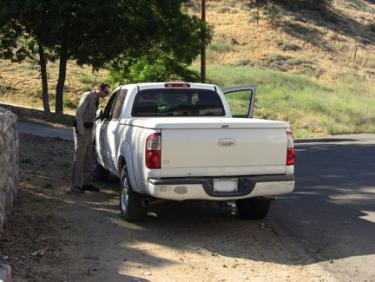 Only a block away, on Circle Drive, the hit and run suspect's truck is examined while the suspect receives medical attention for injuries possibly sustained in the collision. [photo by The Mountain Enterprise]