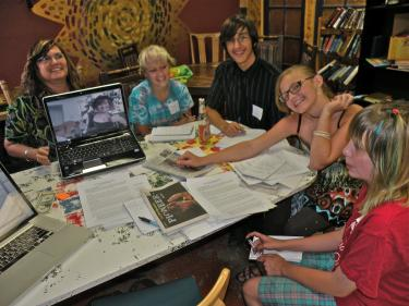 "(l-r) McCASA's Lisa Walter holds the computer from which Sierra Kerr skyped to the first meeting of the TeenBeat core team. Tyfannee Davis, Anthony Levesque, Rhiannon ""Rain"" White and Madison Marasa also attended the orientation with Managing Editor Patric Hedlund (not shown) at the Coffee Cantina July 15."