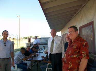 In the background, residents of the Antelope Acres area filled out applications for construction-related jobs for the First Solar AV Solar Ranch One on July 20. It will be a 2,093-acre solar utility. First Solar will also build the NRG solar project. Standing in the foreground (l-r) are Alex Martin (with the community relations team for First Solar), Norm Hickling (5th District Field Deputy for L.A. County Supervisor Michael Antonovich) and Karl Humphreys, who has argued strenuously for concessions from the company to benefit the surrounding communities. He and others in the rural town councils argue that they will be forced to watch the rural landscapes around them be transformed by highly-subsidized green energy developers. They say if they cannot stop these changes, communities deserve to benefit and mitigations need to be in place.