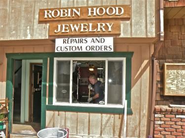 Kip Storz is seen sweeping up glass shards through the shattered front window of Robin Hood Jewelry in Pine Mountain Village on Friday, Aug. 12 at about 10 a.m.