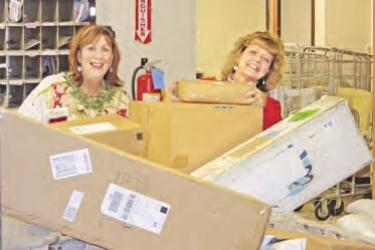 Mary Bollman and Frazier Park Postmaser Kathy Gilbert come up for air amidst hundreds of packages.