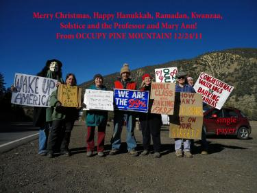 The local Occupy demonstrators sent a greeting to Occupy Good Cheer this holiday season, with Occupy Merry Christmas, Happy Hannukkah, Ramadan, Kwanza, and...almost everything. Artist Peter Gullerud is the one at the left of the photo in the Guy Fawkes costume.