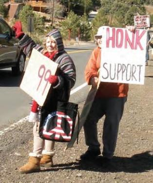 Occupy demonstrators wave, hold signs and count honks in a friendly tail-gate party, tea and cookies spirit.[Hedlund photo]