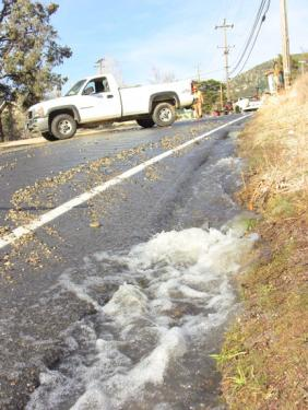 Water runs down Mt. Pinos Way near the intersection with Los Padres Drive (west). [photo by The Mountain Enterprise]