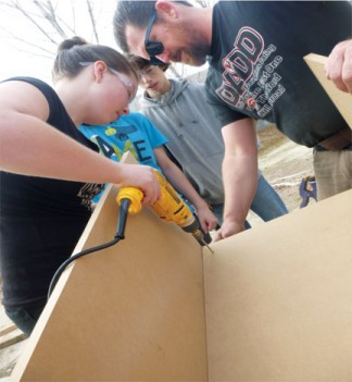 Brianna Edwards drills to help build the station for the human players with supervision from Mr. Kelly. [Lily Hallmark photo]