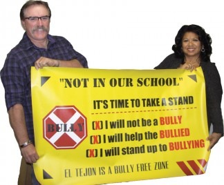 El Tejon Unified School Board President Scott Robinson giving a 'Not In Our School' banner to El Tejon School Principal Rosalie Jimenez. [photo by Patric Hedlund]